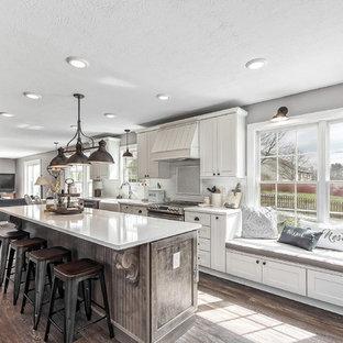 コロンバスの大きいカントリー風おしゃれなキッチン (エプロンフロントシンク、シェーカースタイル扉のキャビネット、白いキャビネット、クオーツストーンカウンター、白いキッチンパネル、サブウェイタイルのキッチンパネル、シルバーの調理設備の、無垢フローリング、茶色い床、白いキッチンカウンター) の写真