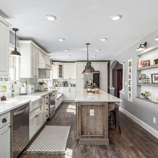 Large farmhouse kitchen photos - Kitchen - large country l-shaped dark wood floor and brown floor kitchen idea in Columbus with a farmhouse sink, shaker cabinets, white cabinets, white backsplash, subway tile backsplash, stainless steel appliances, an island, white countertops and quartz countertops