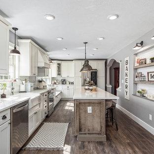 コロンバスの広いカントリー風おしゃれなキッチン (エプロンフロントシンク、シェーカースタイル扉のキャビネット、白いキャビネット、白いキッチンパネル、サブウェイタイルのキッチンパネル、シルバーの調理設備、濃色無垢フローリング、茶色い床、白いキッチンカウンター、クオーツストーンカウンター) の写真
