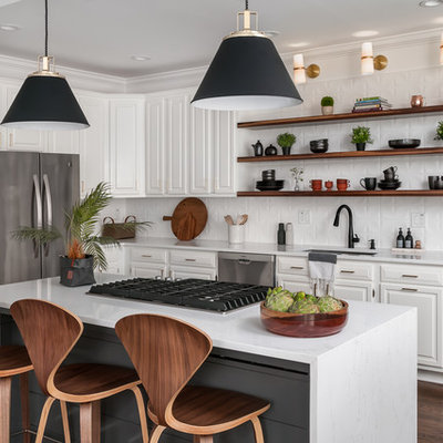 Inspiration for a mid-sized transitional l-shaped dark wood floor and brown floor kitchen remodel in Atlanta with raised-panel cabinets, white cabinets, white backsplash, stainless steel appliances, an island, white countertops, a drop-in sink, quartzite countertops and ceramic backsplash