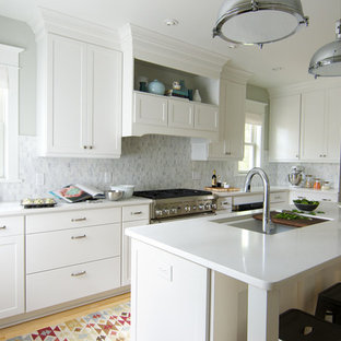 Transitional eat-in kitchen appliance - Eat-in kitchen - transitional l-shaped eat-in kitchen idea in Minneapolis with an undermount sink, flat-panel cabinets, white cabinets, solid surface countertops, gray backsplash, stone tile backsplash and stainless steel appliances