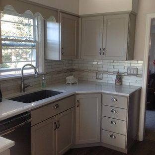 Traditional enclosed kitchen appliance - Example of a classic galley dark wood floor enclosed kitchen design in Seattle with an undermount sink, beaded inset cabinets, gray cabinets, quartz countertops, white backsplash, ceramic backsplash, stainless steel appliances and no island