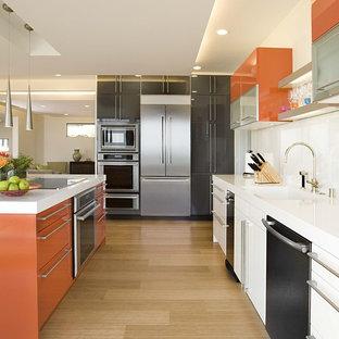 Modern inredning av ett parallellkök, med släta luckor, orange skåp, vitt stänkskydd, glaspanel som stänkskydd, rostfria vitvaror och bambugolv