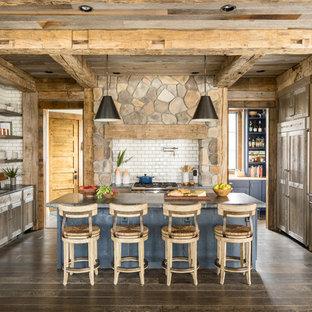 ミネアポリスの広いラスティックスタイルのおしゃれなキッチン (アンダーカウンターシンク、シェーカースタイル扉のキャビネット、中間色木目調キャビネット、ソープストーンカウンター、白いキッチンパネル、セラミックタイルのキッチンパネル、パネルと同色の調理設備、濃色無垢フローリング、茶色い床) の写真