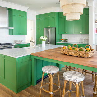 Inspiration for a large beach style l-shaped open plan kitchen in Minneapolis with a farmhouse sink, shaker cabinets, green cabinets, white splashback, subway tile splashback, stainless steel appliances, light hardwood floors, multiple islands, brown floor and marble benchtops.