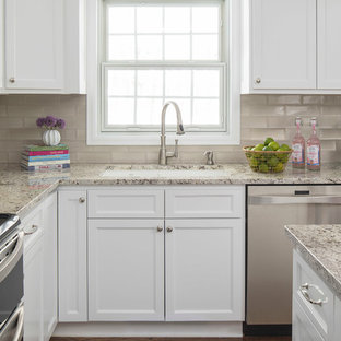 Example of a mid-sized trendy u-shaped medium tone wood floor and brown floor open concept kitchen design in Minneapolis with an undermount sink, shaker cabinets, white cabinets, granite countertops, beige backsplash, subway tile backsplash, stainless steel appliances and an island