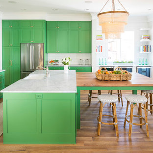 Inspiration for a large beach style l-shaped open plan kitchen in Minneapolis with a belfast sink, shaker cabinets, green cabinets, marble worktops, white splashback, metro tiled splashback, stainless steel appliances, light hardwood flooring, multiple islands and brown floors.
