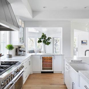 Immagine di una cucina design di medie dimensioni con lavello stile country, ante lisce, ante bianche, top in marmo, paraspruzzi bianco, elettrodomestici in acciaio inossidabile, parquet chiaro, isola, paraspruzzi con piastrelle diamantate e pavimento beige