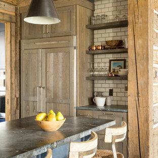 ミネアポリスの大きいラスティックスタイルのおしゃれなキッチン (アンダーカウンターシンク、シェーカースタイル扉のキャビネット、中間色木目調キャビネット、ソープストーンカウンター、白いキッチンパネル、セラミックタイルのキッチンパネル、パネルと同色の調理設備、濃色無垢フローリング、茶色い床) の写真