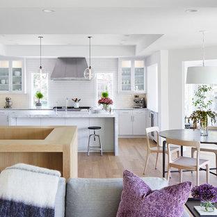 Bild på ett mellanstort nordiskt kök, med en rustik diskho, släta luckor, vita skåp, marmorbänkskiva, vitt stänkskydd, stänkskydd i tunnelbanekakel, rostfria vitvaror, ljust trägolv, en köksö och beiget golv