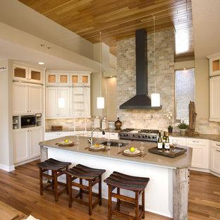 Пример оригинального дизайна: кухня-гостиная в классическом стиле с фасадами в стиле шейкер, белыми фасадами, бежевым фартуком, техникой из нержавеющей стали и фартуком из сланца