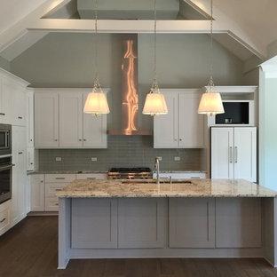 Inspiration för ett mellanstort vintage kök, med en trippel diskho, skåp i shakerstil, vita skåp, granitbänkskiva, grått stänkskydd, stänkskydd i glaskakel, rostfria vitvaror, en köksö, mörkt trägolv och brunt golv
