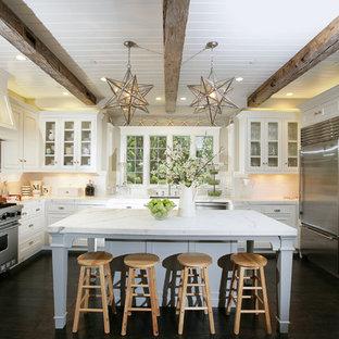 Immagine di una cucina ad U chic con ante di vetro, elettrodomestici in acciaio inossidabile, top in marmo, ante bianche e paraspruzzi bianco
