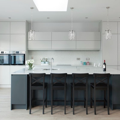 Example of a trendy light wood floor and beige floor kitchen design in Dublin with an undermount sink, flat-panel cabinets, gray cabinets, stainless steel appliances, an island and white countertops