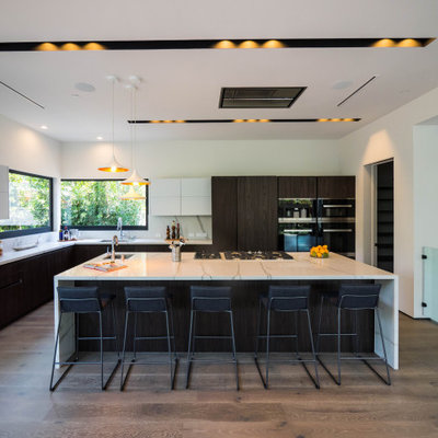 Inspiration for a large contemporary l-shaped medium tone wood floor and brown floor eat-in kitchen remodel in Los Angeles with an undermount sink, flat-panel cabinets, dark wood cabinets, quartz countertops, white backsplash, stone slab backsplash, paneled appliances, an island and white countertops