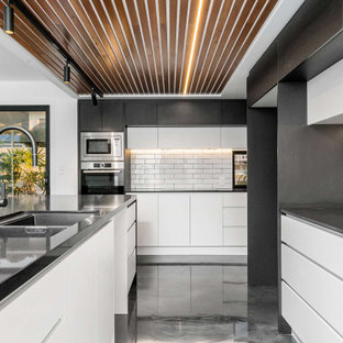 Large contemporary kitchen in Gold Coast - Tweed with an undermount sink, flat-panel cabinets, white cabinets, quartz benchtops, white splashback, subway tile splashback, stainless steel appliances, concrete floors, with island, grey floor, black benchtop and wood.