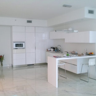 Photo of a small modern l-shaped open plan kitchen in Miami with an undermount sink, flat-panel cabinets, white cabinets, quartzite benchtops, white splashback, stone slab splashback, white appliances and marble floors.