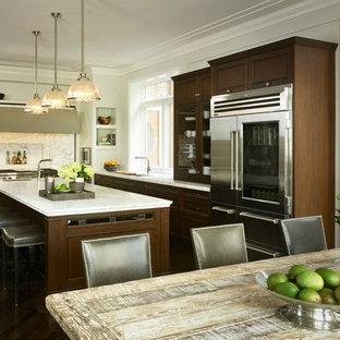 Modelo de cocina comedor en L, clásica, con armarios con paneles empotrados, puertas de armario de madera en tonos medios, salpicadero blanco y salpicadero de losas de piedra