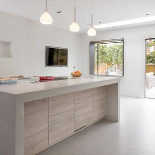 Modelo de cocina actual, extra grande, abierta, con fregadero integrado, armarios con paneles lisos, puertas de armario grises, encimera de cemento, salpicadero blanco, electrodomésticos de acero inoxidable, suelo de baldosas de porcelana y una isla