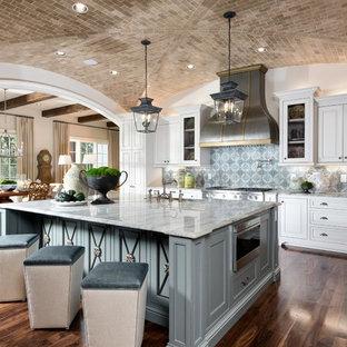Inspiration för stora medelhavsstil kök, med en rustik diskho, vita skåp, granitbänkskiva, blått stänkskydd, stänkskydd i keramik, rostfria vitvaror, mörkt trägolv, en köksö, brunt golv och luckor med upphöjd panel