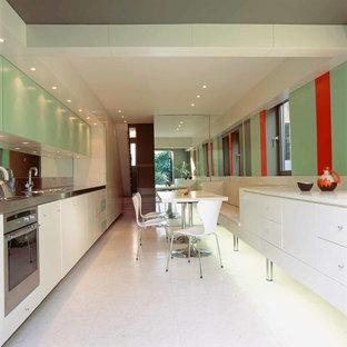 Zweizeilige, Kleine Moderne Wohnküche ohne Insel mit integriertem Waschbecken, flächenbündigen Schrankfronten, grünen Schränken, Edelstahl-Arbeitsplatte, Küchenrückwand in Metallic, Rückwand aus Spiegelfliesen, Küchengeräten aus Edelstahl und Keramikboden in London
