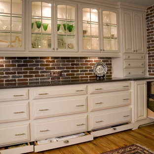 Mid-sized traditional enclosed kitchen appliance - Mid-sized elegant u-shaped light wood floor and brown floor enclosed kitchen photo in Atlanta with an undermount sink, raised-panel cabinets, white cabinets, granite countertops, red backsplash, stone tile backsplash, stainless steel appliances and an island