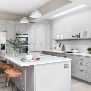 Photo of a traditional l-shaped kitchen in London with a submerged sink, shaker cabinets, grey cabinets, white splashback, stainless steel appliances, an island, grey floors and white worktops.