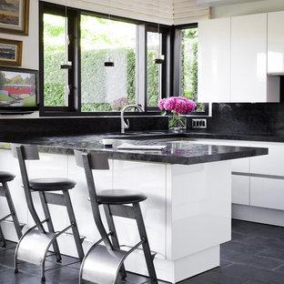 Imagen de cocina en U, moderna, con armarios con paneles lisos, puertas de armario blancas, salpicadero negro y suelo negro