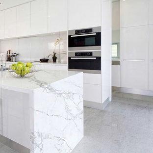 Cette photo montre une cuisine américaine moderne de taille moyenne avec un placard à porte plane, des portes de placard blanches, un sol en carrelage de porcelaine et un îlot central.