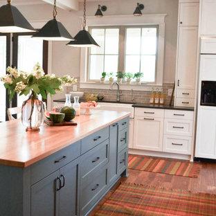 他の地域の広いカントリー風おしゃれなキッチン (エプロンフロントシンク、シェーカースタイル扉のキャビネット、白いキャビネット、御影石カウンター、青いキッチンパネル、サブウェイタイルのキッチンパネル、パネルと同色の調理設備、無垢フローリング、茶色い床、黒いキッチンカウンター、格子天井) の写真