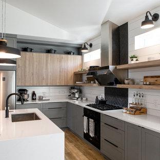 他の地域の中くらいの北欧スタイルのおしゃれなキッチン (アンダーカウンターシンク、シェーカースタイル扉のキャビネット、グレーのキャビネット、人工大理石カウンター、黒いキッチンパネル、セラミックタイルのキッチンパネル、シルバーの調理設備、ラミネートの床、白いキッチンカウンター) の写真
