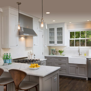 Transitional u-shaped dark wood floor kitchen photo in Columbus with a farmhouse sink, shaker cabinets, gray cabinets, white backsplash, stainless steel appliances and a peninsula