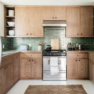 Design ideas for a small tropical u-shaped separate kitchen in Los Angeles with a drop-in sink, flat-panel cabinets, medium wood cabinets, laminate benchtops, green splashback, subway tile splashback, panelled appliances, concrete floors, no island and white floor.
