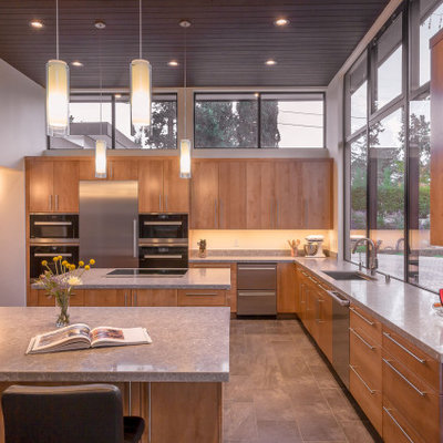 Kitchen - large 1950s u-shaped gray floor and porcelain tile kitchen idea in San Francisco with flat-panel cabinets, light wood cabinets, window backsplash, stainless steel appliances, two islands, gray countertops, an undermount sink, quartz countertops and gray backsplash