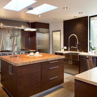 Example of a mid-sized trendy slate floor and brown floor eat-in kitchen design in San Francisco with stainless steel appliances, a farmhouse sink, quartz countertops, flat-panel cabinets, dark wood cabinets, brown backsplash, subway tile backsplash and beige countertops