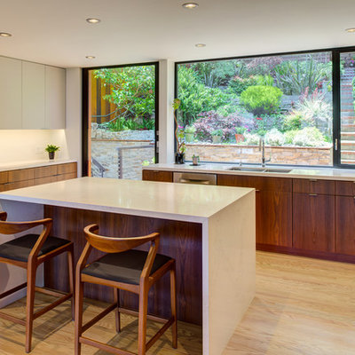 Inspiration for a small contemporary u-shaped light wood floor and beige floor kitchen remodel in San Francisco with flat-panel cabinets, medium tone wood cabinets, quartz countertops, white backsplash, stainless steel appliances, an island, white countertops and an undermount sink