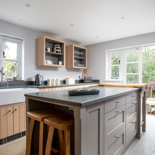 Geschlossene, Zweizeilige, Mittelgroße Maritime Küche mit Landhausspüle, Schrankfronten im Shaker-Stil, hellbraunen Holzschränken, Kücheninsel, beigem Boden, grauer Arbeitsplatte, Küchenrückwand in Grau und Porzellan-Bodenfliesen in Gloucestershire
