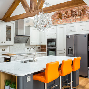 Large country l-shaped kitchen in Gloucestershire with a submerged sink, white cabinets, black appliances, an island, brown floors, white worktops, shaker cabinets, white splashback, stone slab splashback, medium hardwood flooring and a vaulted ceiling.