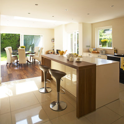 Trendy eat-in kitchen photo in Dublin with wood countertops