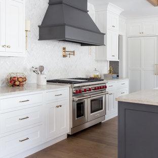 ニューヨークのトランジショナルスタイルのおしゃれなキッチン (エプロンフロントシンク、シェーカースタイル扉のキャビネット、白いキャビネット、白いキッチンパネル、シルバーの調理設備、無垢フローリング、茶色い床、ベージュのキッチンカウンター) の写真
