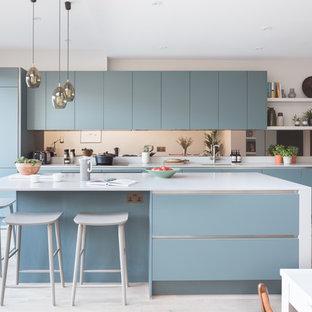 ロンドンの中サイズのコンテンポラリースタイルのおしゃれなキッチン (アンダーカウンターシンク、フラットパネル扉のキャビネット、青いキャビネット、ベージュの床、ミラータイルのキッチンパネル、パネルと同色の調理設備) の写真