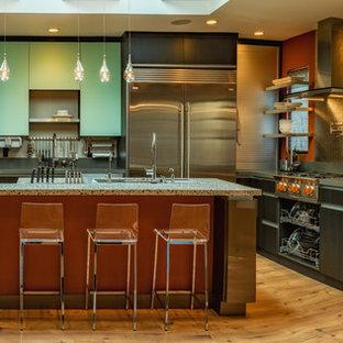 Modern inredning av ett stort kök, med en undermonterad diskho, släta luckor, grå skåp, bänkskiva i återvunnet glas, färgglada vitvaror, korkgolv och en köksö
