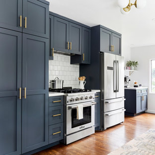 Design ideas for a mid-sized beach style galley separate kitchen in Los Angeles with a farmhouse sink, shaker cabinets, blue cabinets, quartz benchtops, white splashback, subway tile splashback, stainless steel appliances, dark hardwood floors, no island, brown floor and blue benchtop.