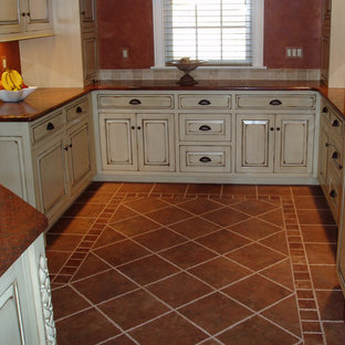 Mid-sized southwestern enclosed kitchen appliance - Example of a mid-sized southwest u-shaped ceramic floor and brown floor enclosed kitchen design in Boston with raised-panel cabinets, beige cabinets, granite countertops, red backsplash, paneled appliances, no island and red countertops