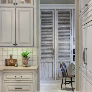 Photo of a mid-sized traditional l-shaped kitchen pantry in Houston with a drop-in sink, raised-panel cabinets, beige cabinets, limestone benchtops, beige splashback, ceramic splashback, stainless steel appliances, limestone floors and multiple islands.