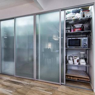 サンフランシスコの小さいモダンスタイルのおしゃれなキッチン (シングルシンク、フラットパネル扉のキャビネット、黄色いキャビネット、人工大理石カウンター、シルバーの調理設備の、メタリックのキッチンパネル、石タイルのキッチンパネル、磁器タイルの床) の写真