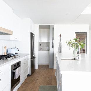 ゴールドコーストの大きいビーチスタイルのおしゃれなキッチン (アンダーカウンターシンク、シェーカースタイル扉のキャビネット、グレーのキャビネット、クオーツストーンカウンター、ベージュキッチンパネル、磁器タイルのキッチンパネル、シルバーの調理設備の、クッションフロア、茶色い床、白いキッチンカウンター) の写真