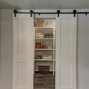 Large farmhouse kitchen pantry designs - Large farmhouse l-shaped porcelain tile kitchen pantry photo in Phoenix with shaker cabinets, white cabinets, granite countertops, an island, black backsplash, stone slab backsplash, stainless steel appliances and a double-bowl sink