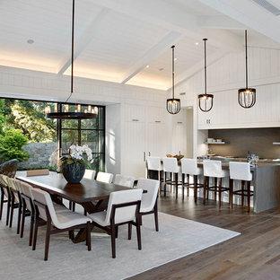 Bild på ett stort lantligt grå grått kök och matrum, med vita skåp, grått stänkskydd, en köksö, bänkskiva i kalksten, stänkskydd i kalk, integrerade vitvaror, mellanmörkt trägolv och brunt golv