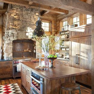 アトランタのラスティックスタイルのおしゃれなキッチン (パネルと同色の調理設備、木材カウンター、落し込みパネル扉のキャビネット、中間色木目調キャビネット、茶色いキッチンパネル、メタルタイルのキッチンパネル) の写真
